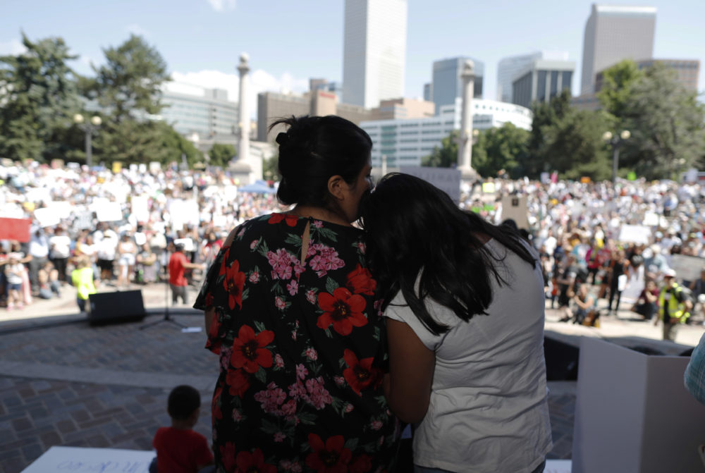 Brenda Villa, left, comforts her 11-year-old daughter, Kathryn, after speaking during an immigration rally and protest in Civic Center Park Saturday, June 30, 2018, in downtown Denver. (David Zalubowski/AP)