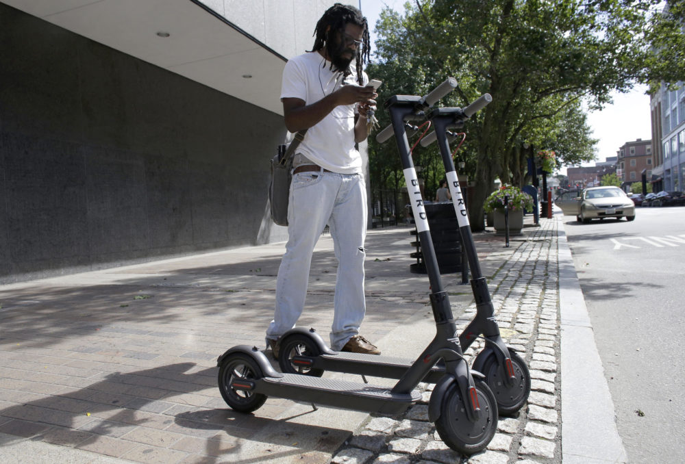 Vatic Kuumba, of Providence, R.I., prepares to ride a Bird electric scooter in downtown Providence Tuesday, July 24, 2018. (Steven Senne/AP)