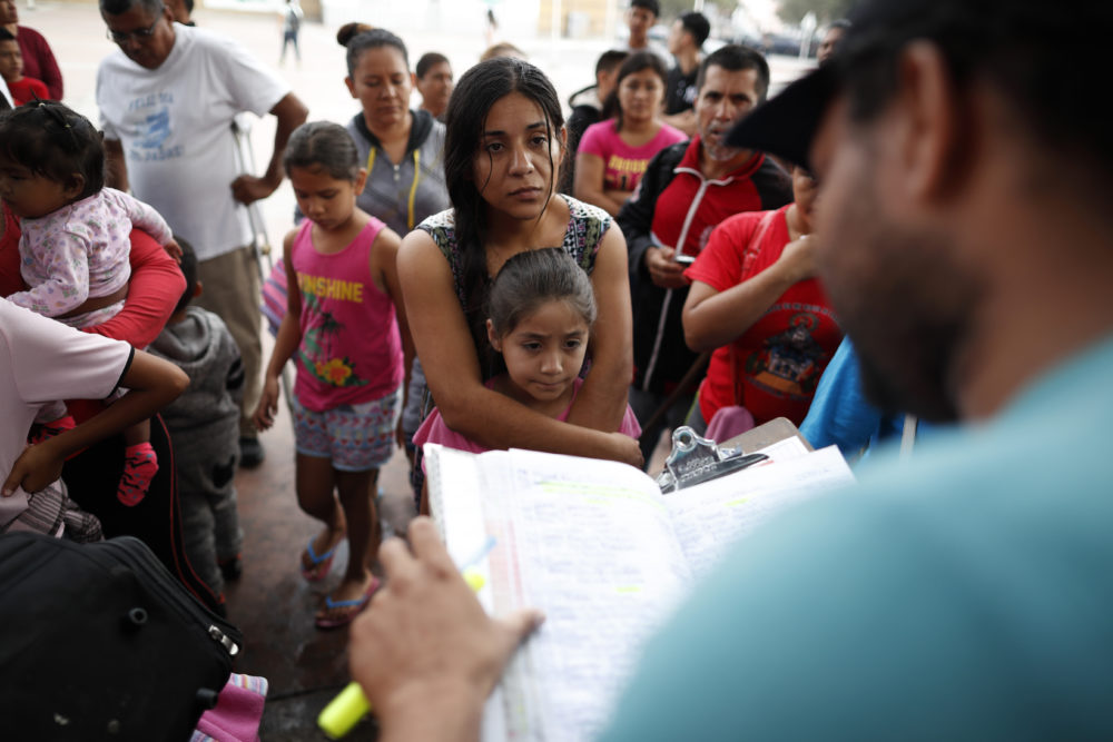 A woman from the Mexican state of Michoacan who did not give her name stands with her daughter as names are read off a list of people who will cross into the United States to begin the process of applying for asylum Thursday, July 26, 2018. (Gregory Bull/AP)