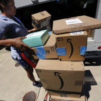 In this July 19, 2018, photo, a U.S. postal carrier delivers Amazon orders to an apartment complex in downtown Pittsburgh. (Gene J. Puskar/AP)