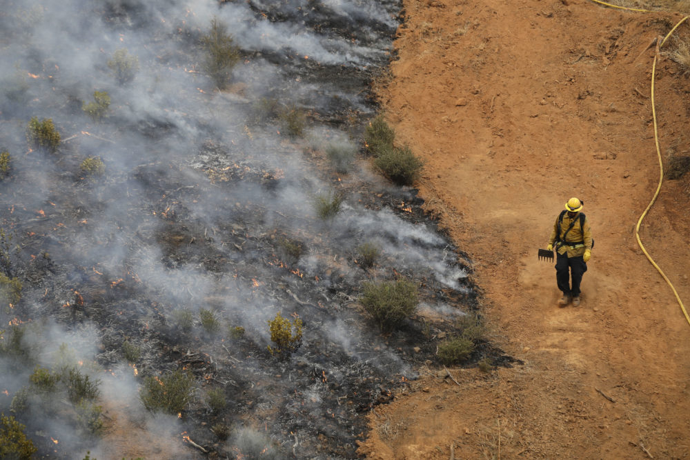 A firefighter walks along a containment line while battling a wildfire Saturday, July 28, 2018, in Redding, Calif. (Marcio Jose Sanchez/AP)