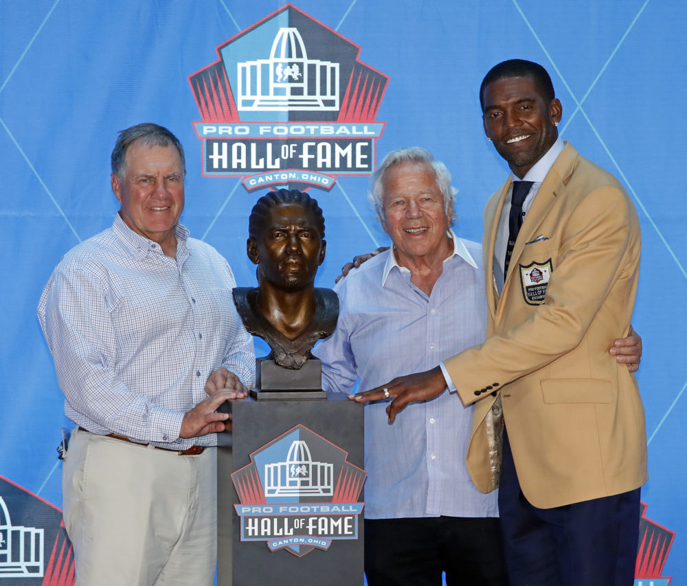 Former NFL wide receiver Randy Moss, right, poses with New England Patriots owner Robert Kraft, center, and coach Bill Belichick and a bust of himself during inductions at the Pro Football Hall of Fame, Saturday, Aug. 4, 2018 in Canton, Ohio. (Gene J. Puskar/AP)