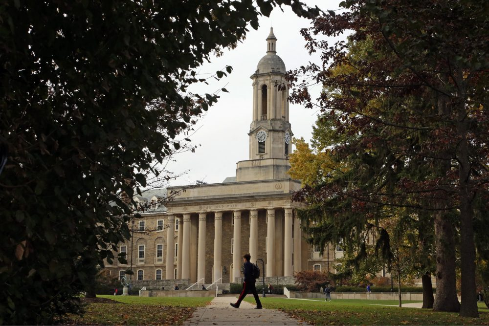 In this Nov. 9, 2017, file photo people walk by Old Main on the Penn State University main campus in State College, Penn.(Gene J. Puskar, File/AP)