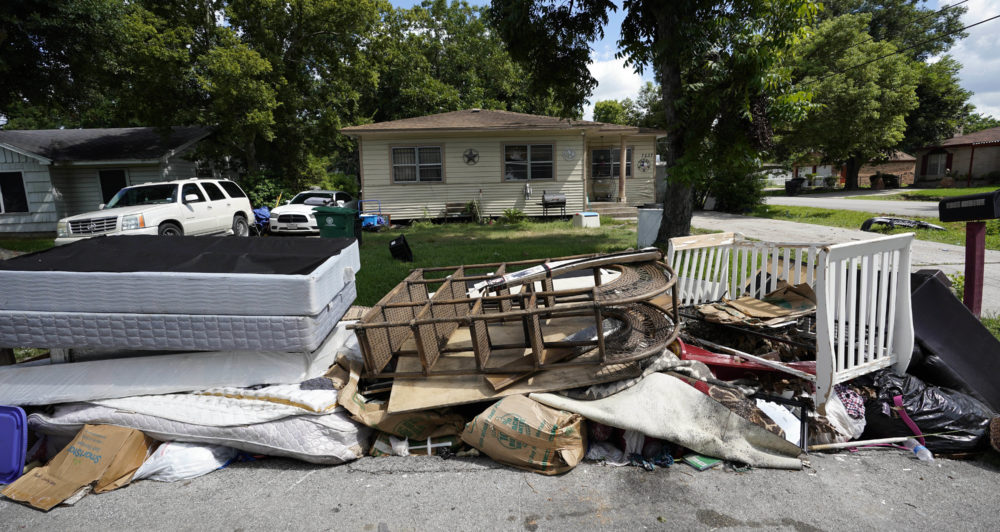 In this Aug. 9, 2018 photo, recently removed flood-damaged debris sits outside a home in Houston. Hurricane Harvey has been described as the storm that did not discriminate, damaging neighborhoods both rich and poor. But community and grassroots leaders say that a year after the storm, those having the hardest time recovering are residents who live in some of the poorest areas hit hardest by Harvey. (David J. Phillip/AP)