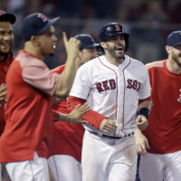 Boston Red Sox's J.D. Martinez, second from right, celebrates with teammates after scoring after Eduardo Nunez reached first base on a throwing error, breaking a 7-7 tie, during the bottom of the ninth inning of a baseball game at Fenway Park in Boston, Tuesday, Aug. 28, 2018. The Red Sox won 8-7. (Charles Krupa/AP)