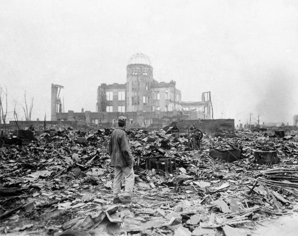 An allied correspondent stands in the rubble in front of the shell of a building that once was a movie theater in Hiroshima, Japan, a month after the first atomic bomb ever used in warfare was dropped by the U.S. on Aug. 6, 1945. (Stanley Troutman/AP)