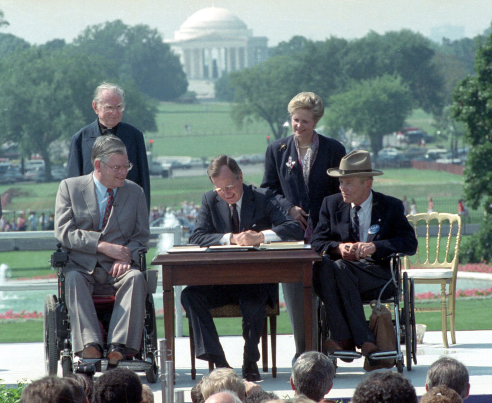 In this July 26, 1990 file photo, President George H. W. Bush signs the Americans with Disabilities Act during a ceremony on the South Lawn of the White House. (Barry Thumma/AP)