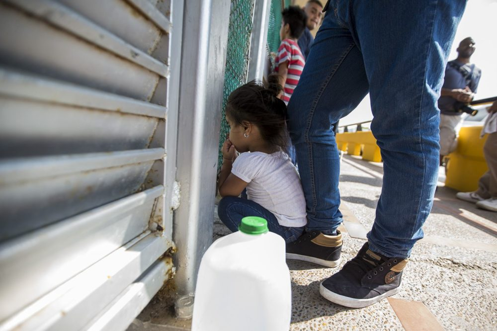 A 3-year-old from Honduras peers through a fence at the U.S.-Mexico border while her family waits to apply for asylum. (Jesse Costa/WBUR)