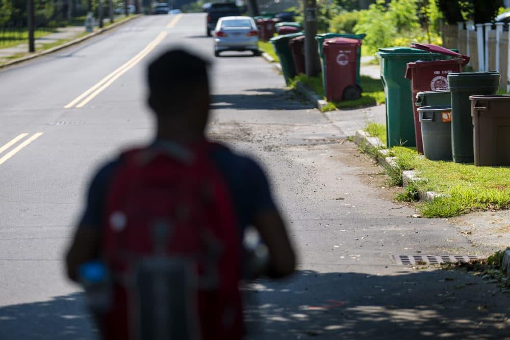 Lowell recycling enforcement coordinator Bora Chhun walks down Beacon Street in Lowell. (Jesse Costa/WBUR)