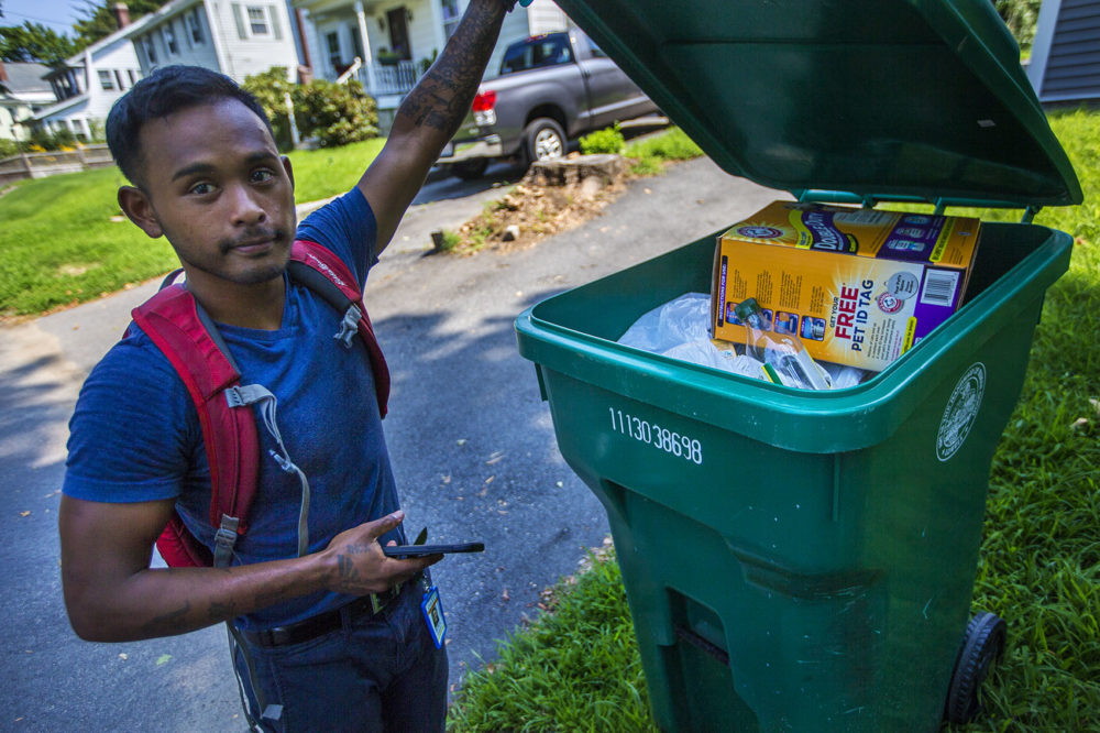 Lowell recycling enforcement coordinator Bora Chhun checks a recycling bin for non-recycable items on Beacon Street in Lowell. (Jesse Costa/WBUR)