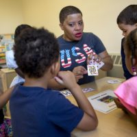 Teacher Nicole Parker-Mondon sits at a table with students, using playing cards as a teaching aid. (Robin Lubbock/WBUR)