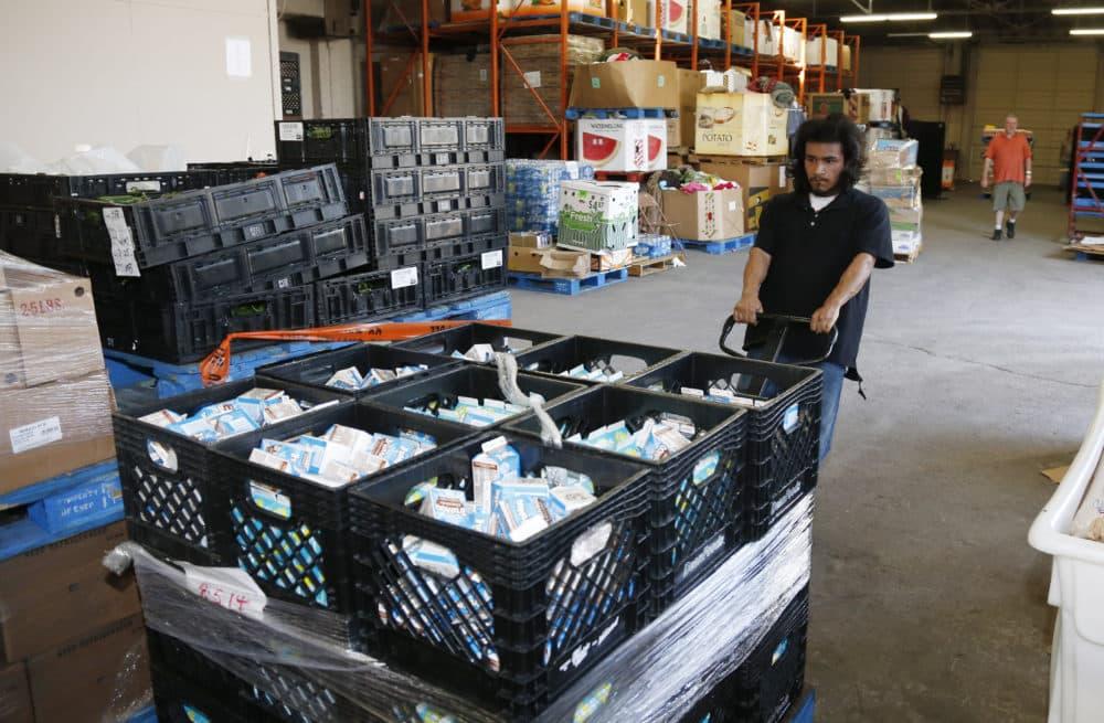 Joseph Elliote moves a pallet full of milk in the Jesus House homeless shelter warehouse in Oklahoma City. (AP Photo)