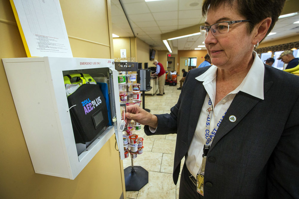 Pam Bellino, patient safety manager for VA Boston, opens an AED box located in the cafeteria at the West Roxbury VA Medical Center, with the naloxone kit, the blue pouch, tucked on the side next to the defibrillator. (Jesse Costa/WBUR)