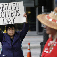Lovella Black Bear, left, holds a sign calling for the abolishment of Columbus Day during a 2015 demonstration for Indigenous Peoples' Day in Seattle. (Elaine Thompson/AP)