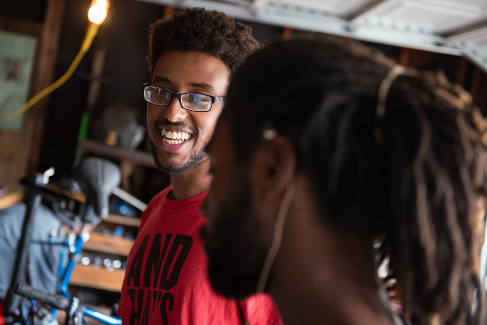 Samson Tarefe, left, laughs as he chats with Antonio Ballard, right, in the Biker Boyz & Girlz Shop in Indianapolis. (Lucas Carter for Here & Now)