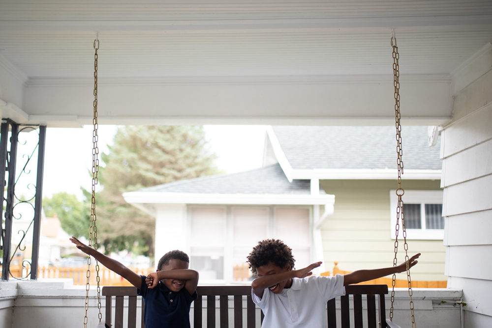 Ocean, 6, and Josh, 8, dab on the front porch adjacent to the Biker Boyz & Girlz Shop in Indianapolis. (Lucas Carter for Here & Now)
