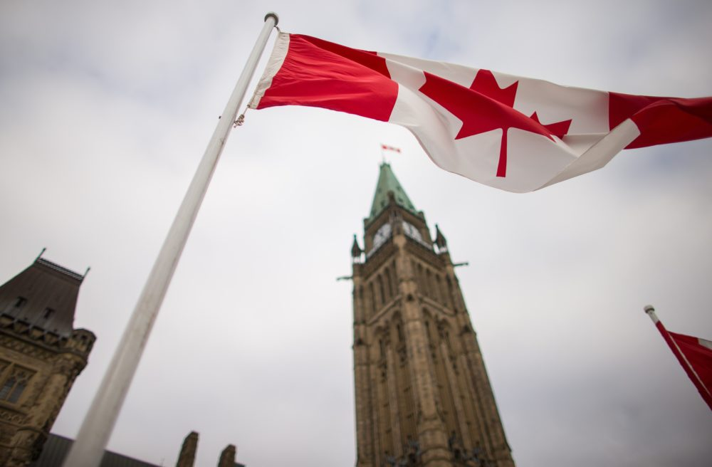 A Canadian flag flies in front of the peace tower on Parliament Hill in Ottawa, Canada. (Geoff Robins/AFP/Getty Images)