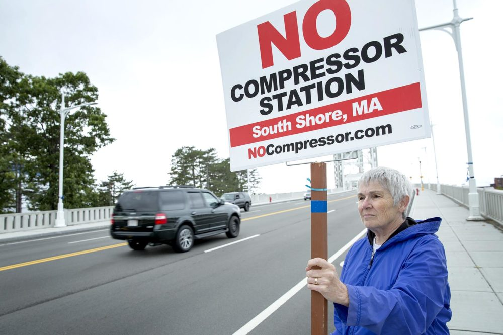 Mernie Clifton demonstrates against the proposed gas compressor, as cars drive by on the Fore River Bridge in Weymouth. (Robin Lubbock/WBUR)