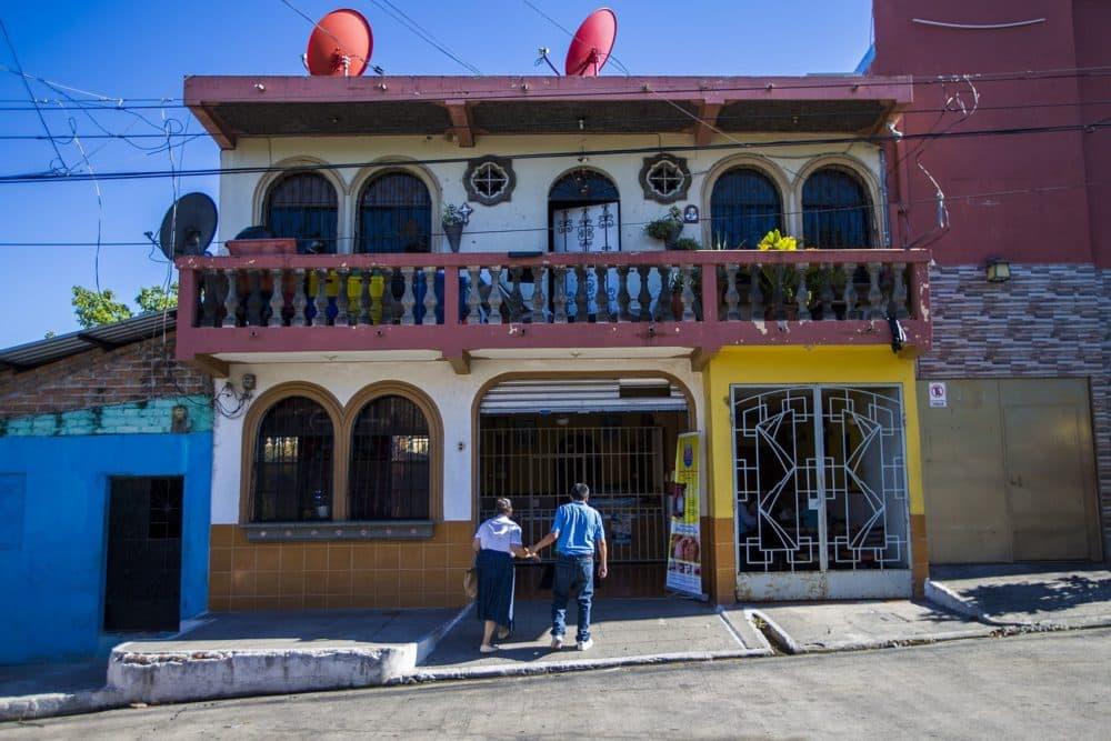 A couple walk hand-in-hand into Panaderia Pacita Quintanilla in San Vicente, El Salvador. (Jesse Costa/WBUR)