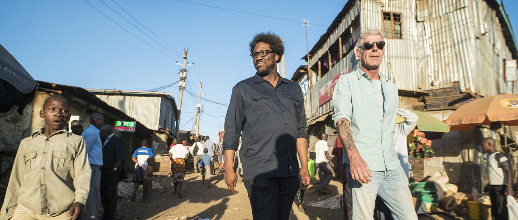 """Anthony Bourdain (right) with W. Kamau Bell in the Kibera slums in Nairobi, Kenya, while filming the first episode of the final season of CNN's """"Parts Unknown."""" (Courtesy David Scott Holloway via CNN)"""