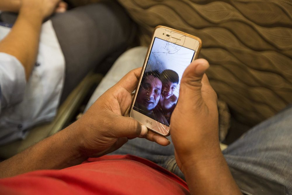 Carlos Alexis Hernandez Licona shows a selfie video of his 6-year-old son, Carlos Gabriel, and himself having fun while singing a song during a video made to send home. (Jesse Costa/WBUR)