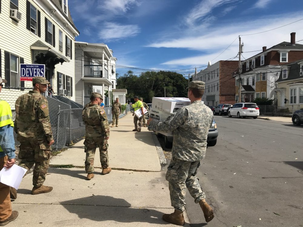 National Guardsmen walk through the streets of Lawrence on Saturday, distributing hot plates to residents who were left without gas. (Quincy Walters/WBUR)