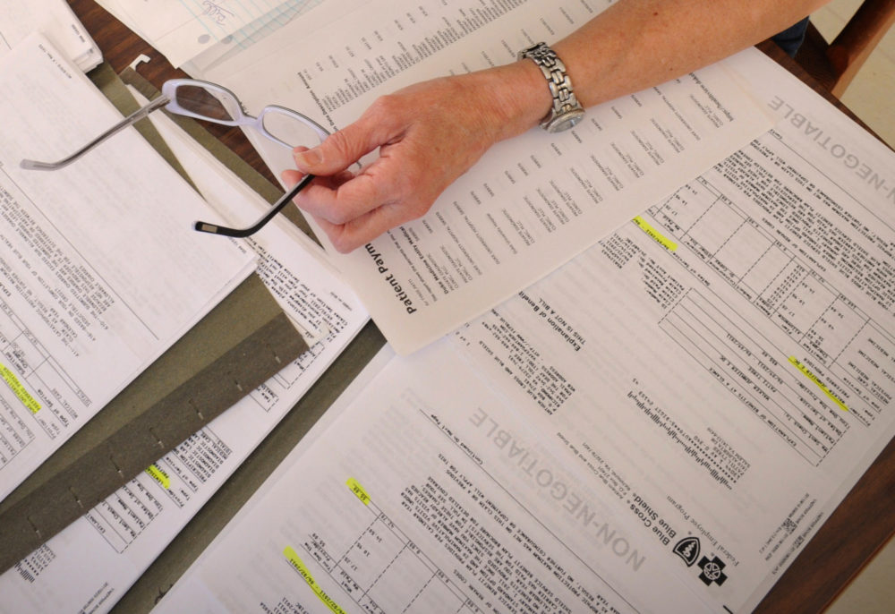 Medical bills are spread out on the kitchen table of a cancer patient. (AP File Photo)