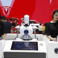 """FILE - In this April 26, 2018, file photo, a robot assist receptionist is seen at the booth of a Chinese automaker during the China Auto 2018 show in Beijing, China. Under President Xi Jinping, a program known as """"Made in China 2025"""" aims to make China a tech superpower by advancing development of industries that in addition to semiconductors includes artificial intelligence, pharmaceuticals and electric vehicles. (AP Photo/Ng Han Guan, File)"""