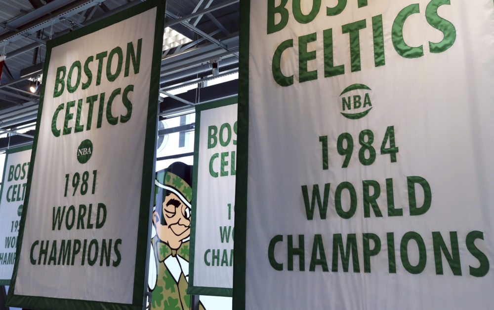 Lucky the Leprechaun, the Boston Celtics team logo, peers out from in between Celtics championship banners hanging in the team's new practice facility. (Elise Amendola/AP)