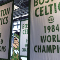 Lucky the Leprechaun, the Boston Celtics team logo, peers out from in between Celtics championship banners hanging in their new basketball team practice facility. (Elise Amendola/AP)