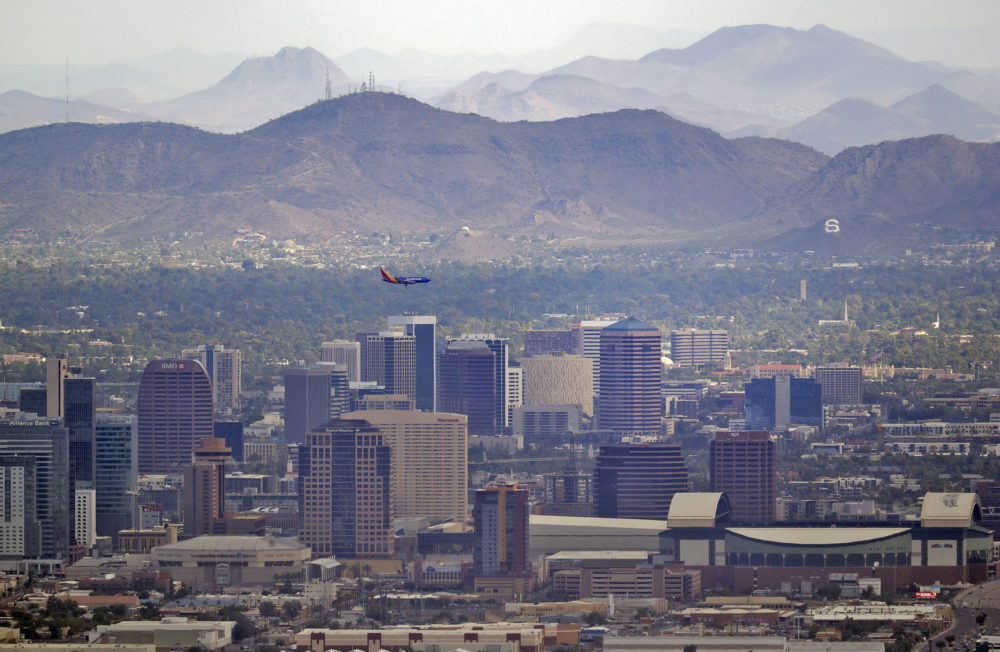 A jet comes in for an approach over downtown early Tuesday, July 24, 2018 in Phoenix, as temperatures exceed 100 degrees in the morning hours. (Matt York/AP)