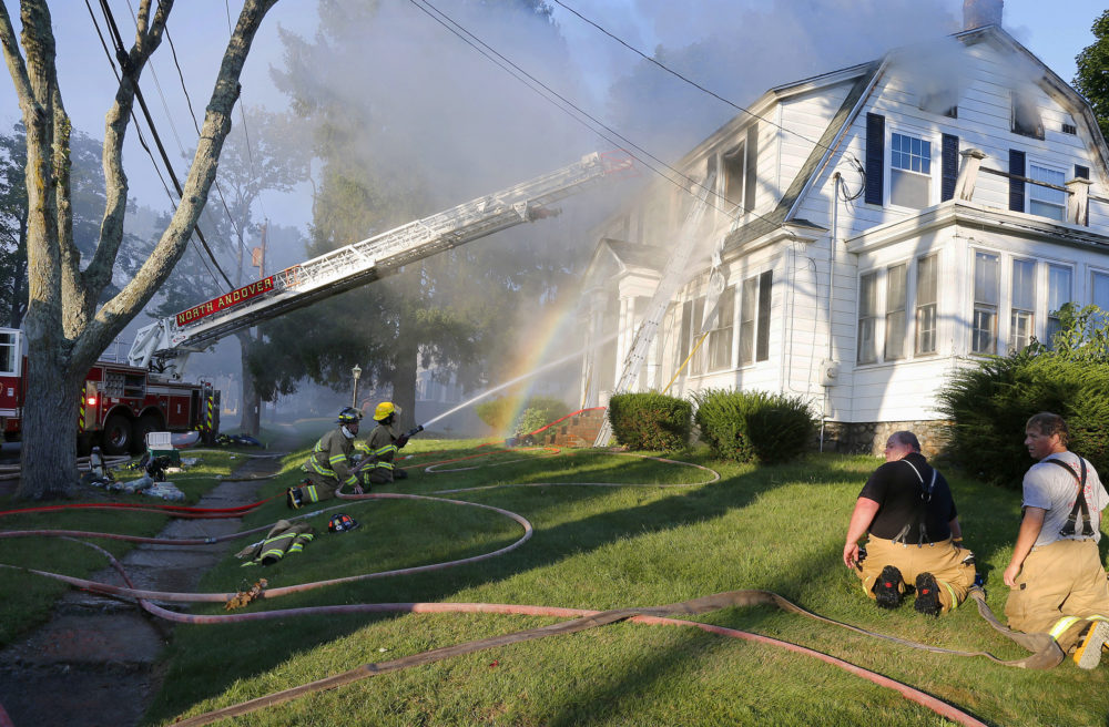 Firefighters battle a house fire on Herrick Road in North Andover. (Mary Schwalm/AP)