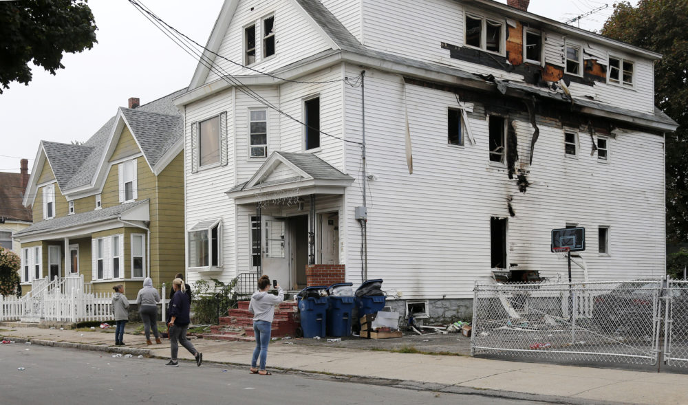 Lawrence residents stop to take photos of a house on Bowdoin Street in Lawrence Friday. (Mary Schwalm/AP)