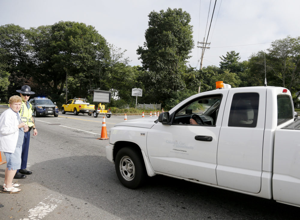 A Columbia Gas truck passes through a roadblock as a member of the state police talks to a pedestrian on Route 114 in North Andover at the Lawrence city line (Mary Schwalm/AP)
