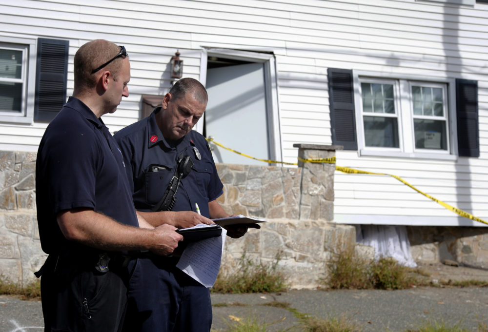 Fire inspectors take notes outside a house that was blown off its foundation on Kingston Street in Lawrence. (Mary Schwalm/AP)