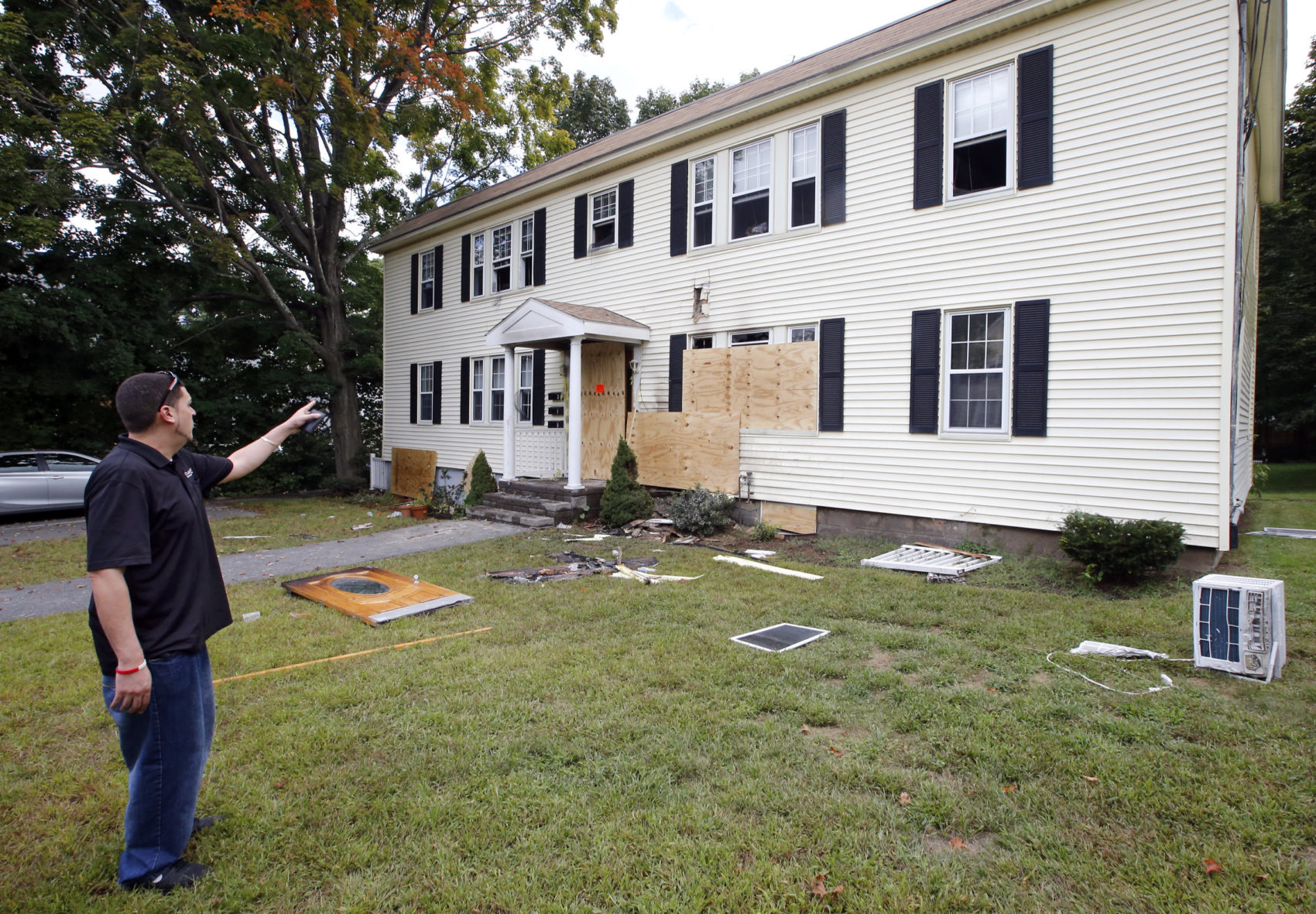 Josef Koch of Clean Joe, a disaster restoration service, looks over a house damaged by fire Friday in Andover. (Winslow Townson/AP)