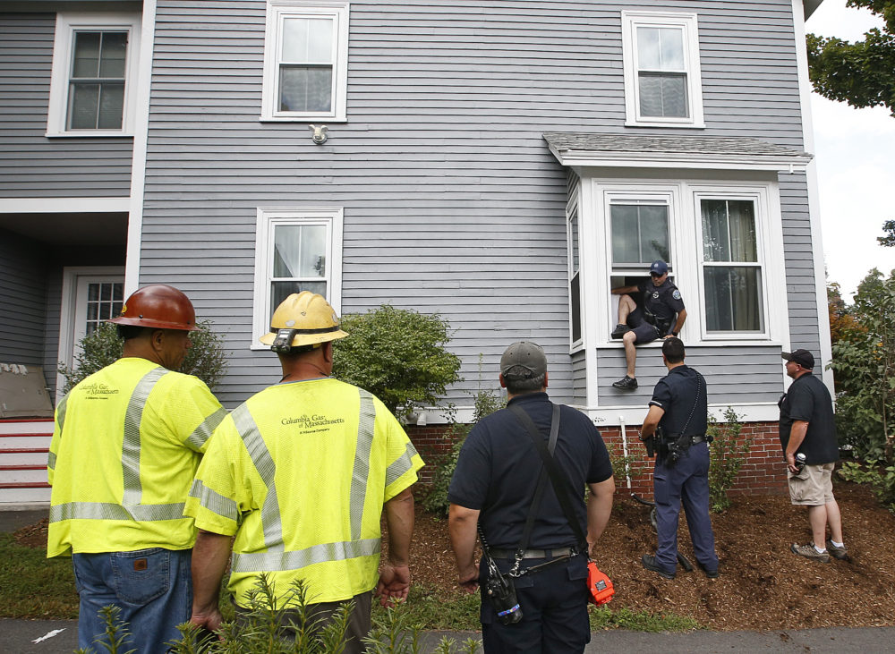 As Columbia Gas employees look on, an Andover police officer comes out the window of an evacuated house after checking that there is no presence of gas and that the gas in the house is turned off Friday in Andover. (Winslow Townson/AP)
