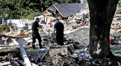 Fire investigators pause while searching the debris at a home which exploded last week following a gas line failure in Lawrence, Mass., Friday, Sept. 21, 2018. Nearly 9,000 homes and businesses may be without gas for weeks as investigators continue to probe what set off the explosions. (Charles Krupa/AP)