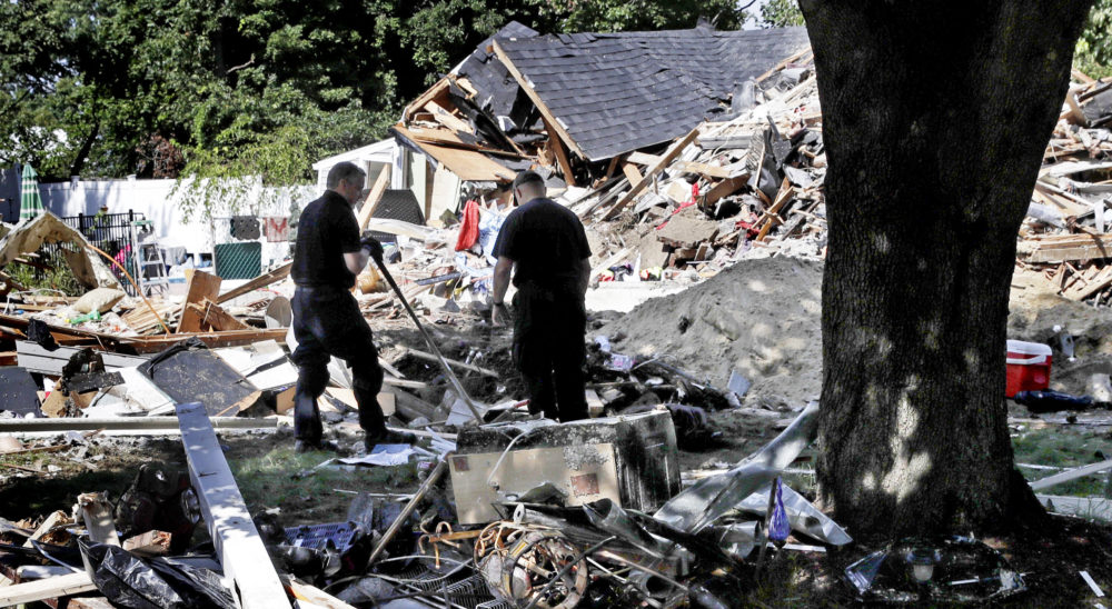 Fire investigators pause while searching the debris at a home which exploded following a gas line failure in Lawrence. (Charles Krupa/AP)