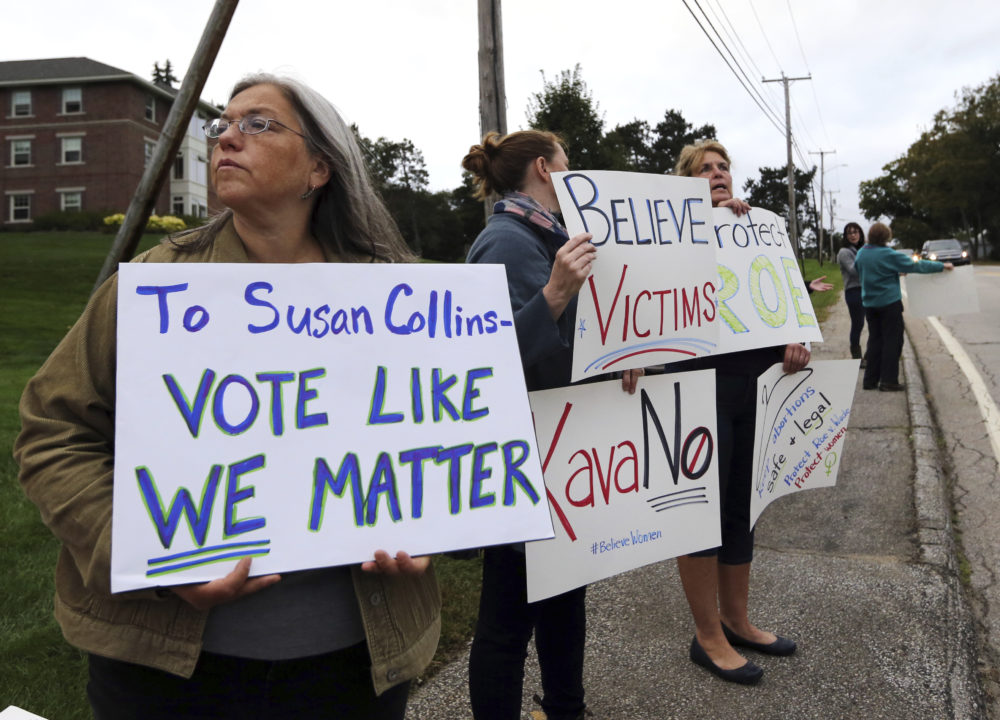 "Demonstrators hold signs outside Saint Anselm College, Friday, Sept. 21, 2018, in Manchester, N.H., where U.S. Sen. Susan Collins, R-Maine, considered one of the few possible Republican ""no"" votes on Supreme Court nominee Brett Kavanaugh, is scheduled to speak. (Elise Amendola/AP)"