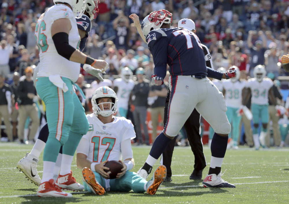 New England Patriots defensive tackle Adam Butler, right, celebrates after sacking Miami Dolphins quarterback Ryan Tannehill (17) during the second half of an NFL football game, Sunday, Sept. 30, 2018, in Foxborough, Mass. (AP Photo/Elise Amendola)