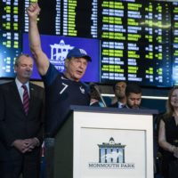 Former New Jersey State Senator Raymond Lesniak, the legal champion in the Supreme Court decision to legalize gambling, raises his hand while speaking on June 14, 2018 before Governor Phil Murphy to placed the first bet at the Monmouth Park Sports Book on the first day of legal sports betting in the state in New Jersey. (DOMINICK REUTER / AFP/Getty Images)