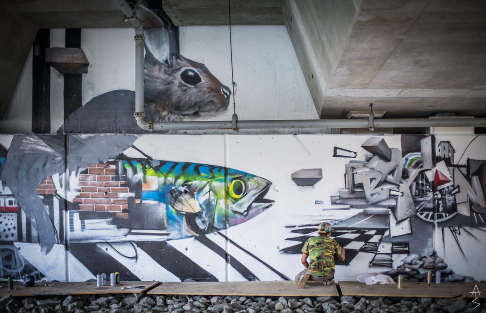 Percy Fortini-Wright paints his mural under the overpass. (Courtesy Adam Straughn)