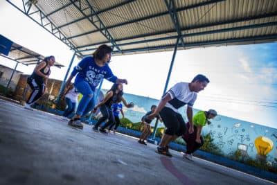 Volunteers for Glasswing International lead members of the Glee club in a dance routine at a school in Las Palmas, San Salvador, El Salvador. (Jesse Costa/WBUR)