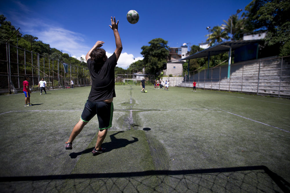 Young boys and teenagers gather at the soccer field in Las Palmas as part of Glasswing International's soccer club. (Jesse Costa/WBUR)