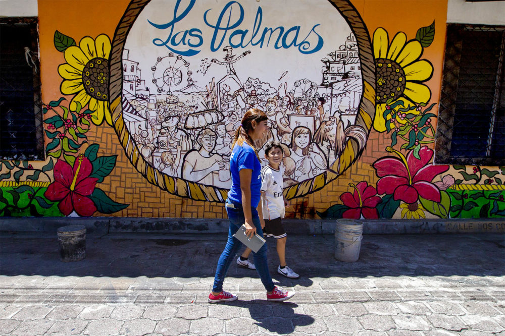 A Glasswing International staff member walks through town with a young boy who lives in Las Palmas. (Jesse Costa/WBUR)