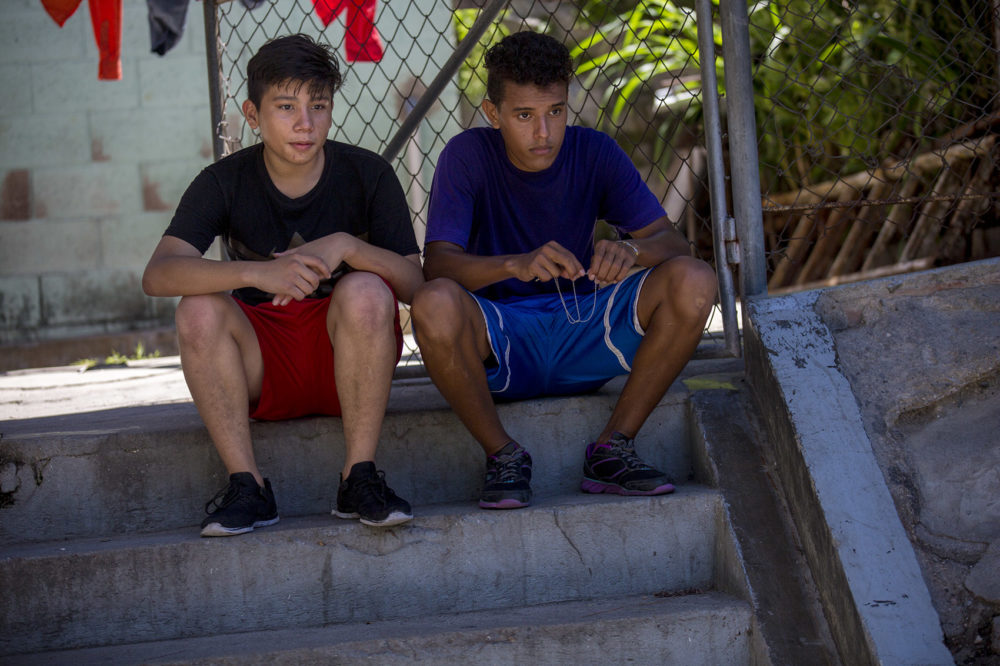 Two Salvadoran teenaged boys sit on steps in the shade while taking a break from playing soccer at a field in the community of Las Palmas in San Salvador. (Jesse Costa/WBUR)