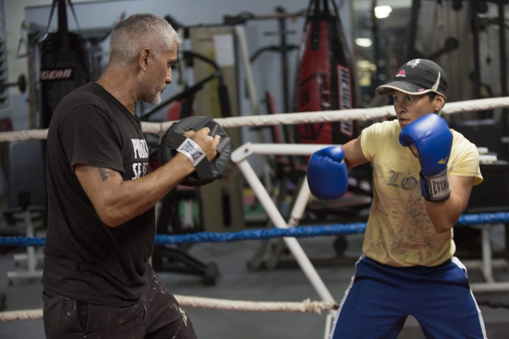 Carolin Camacho Flores, right, trains with Ruben Flores at the La Mesa Fitness Center in Caguas. (Jesse Costa/WBUR)