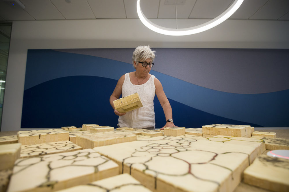 Jodi Colella sets up blocks on a conference room table to prepare her piece to be displayed on the 10th floor in the Boston Consulting Group's building in the Seaport. (Jesse Costa/WBUR)