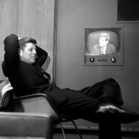 In April 1960, Sen. John F. Kennedy, Democratic presidential nominee, sits next to a playback of his televised appearance in Milwaukee, Wis. for the Wisconsin presidential primary two days later. (AP)